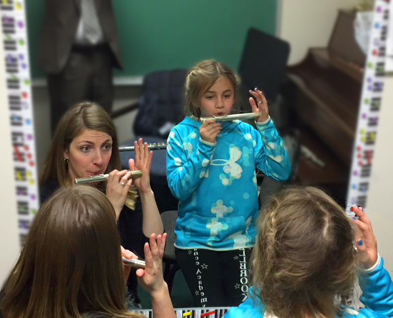 Marissa Rose helps a student make their first sound on the flute
